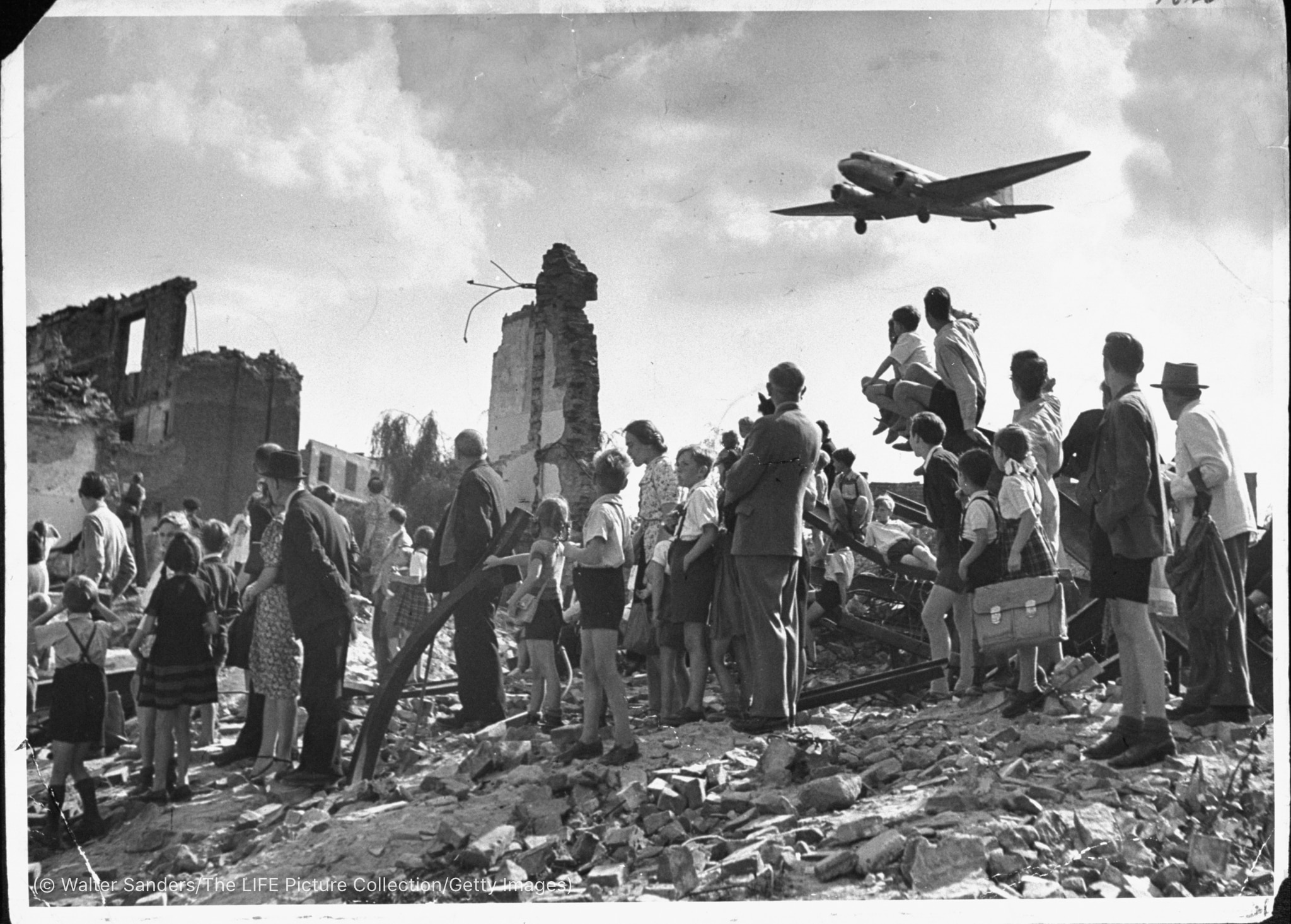 Aircraft overhead, people in ruins looking up at it (© Walter Sanders/LIFE Picture Collection/Getty Images)