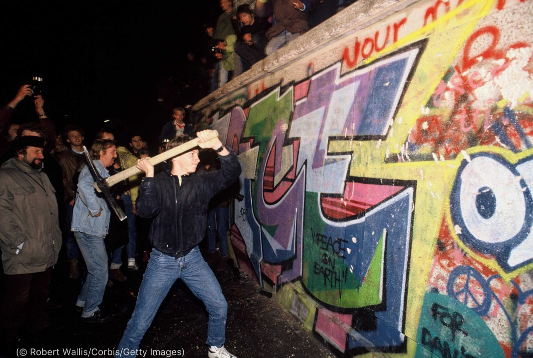 People watching man swing pickax against wall covered with graffiti (© Robert Wallis/Corbis/Getty Images)