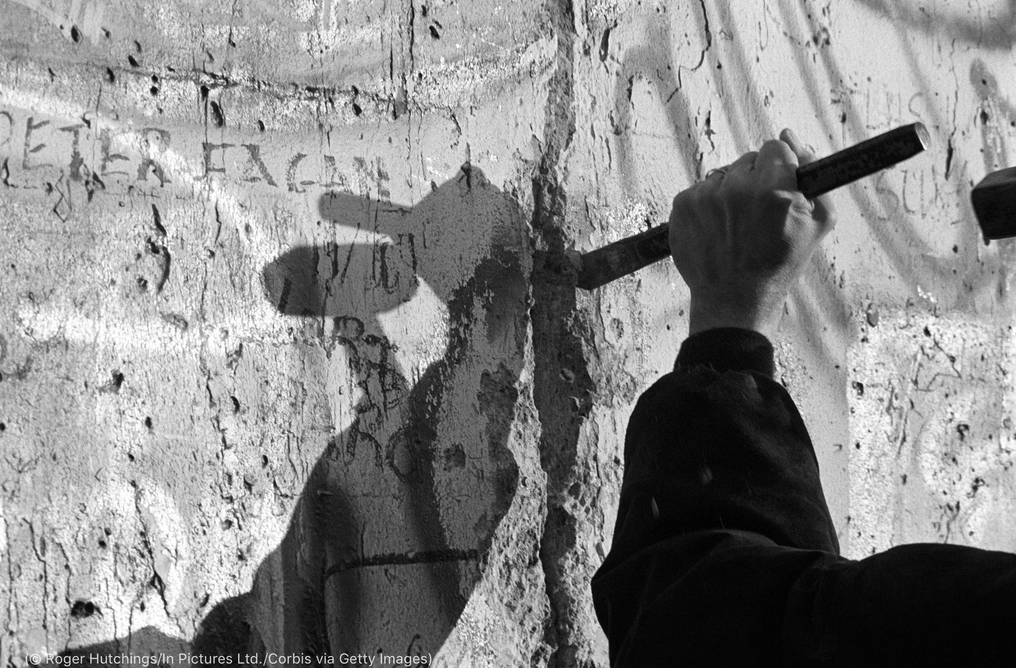 Une personne taillant dans un mur (© Roger Hutchings/In Pictures Ltd./Corbis via Getty Images)