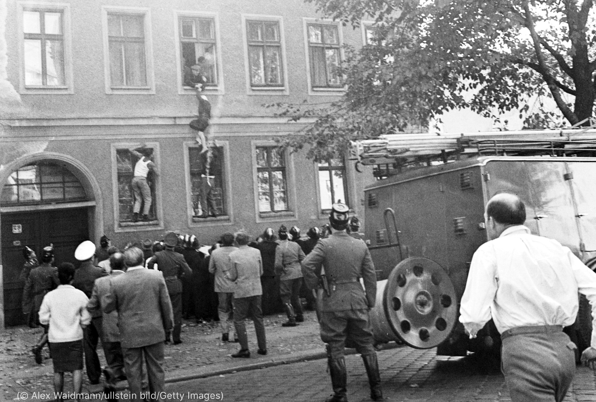 Woman dangling from window, crowd gathered below (© Alex Waidmann/ullstein bild/Getty Images)