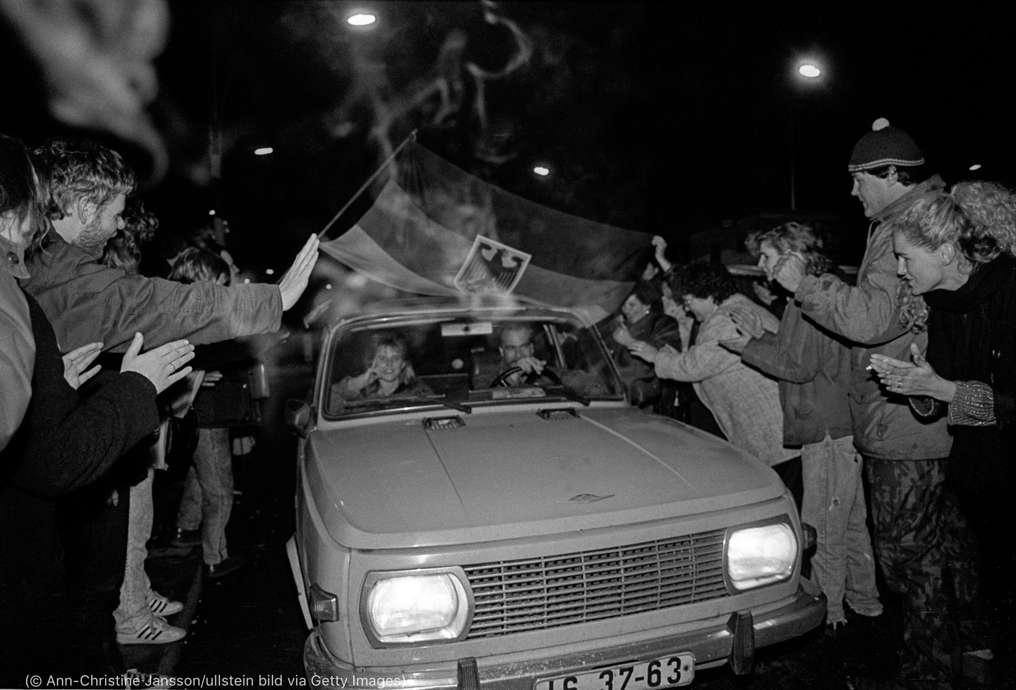Des gens faisant la fête autour d'une voiture (© Ann-Christine Jansson/ullstein bild via Getty Images)