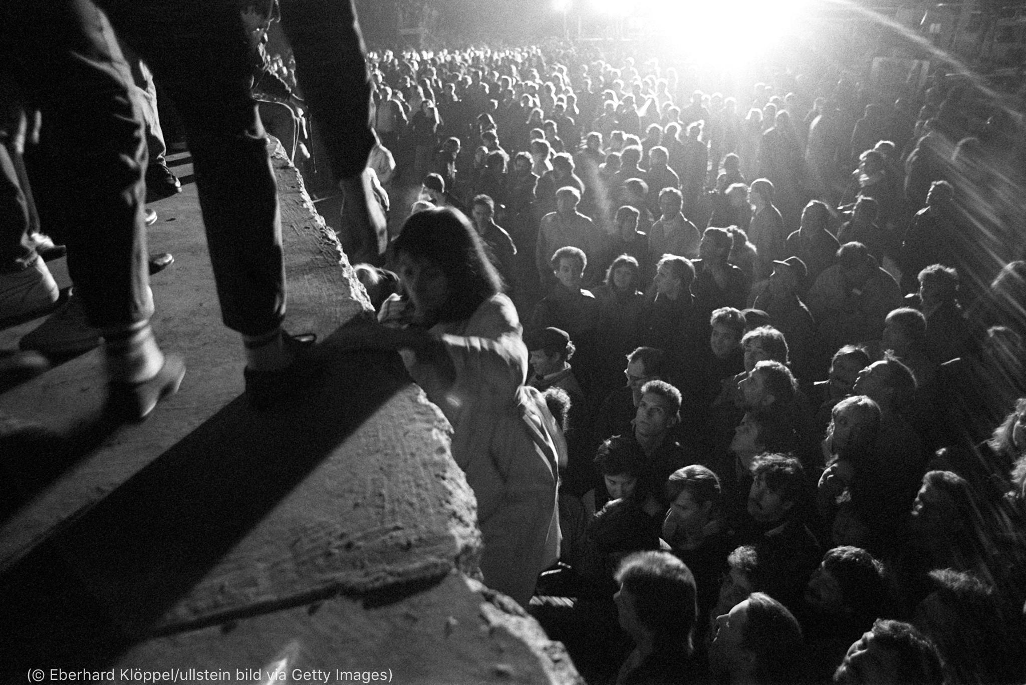 Une femme escaladant un mur devant une foule rassemblée en contrebas (© Eberhard Klöppel/ullstein bild via Getty Images)