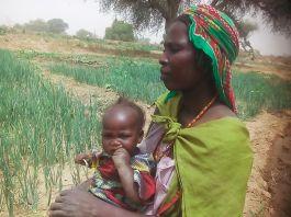 '法蒂玛'抱着女儿站在田里(© Lutheran World Federation)