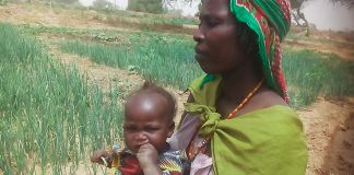 'Fatima' holding her daughter in a field (© Lutheran World Federation)