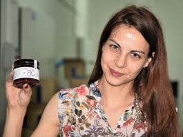 Woman holding up small jar (Mirjana Vukša Zavišić/USAID)