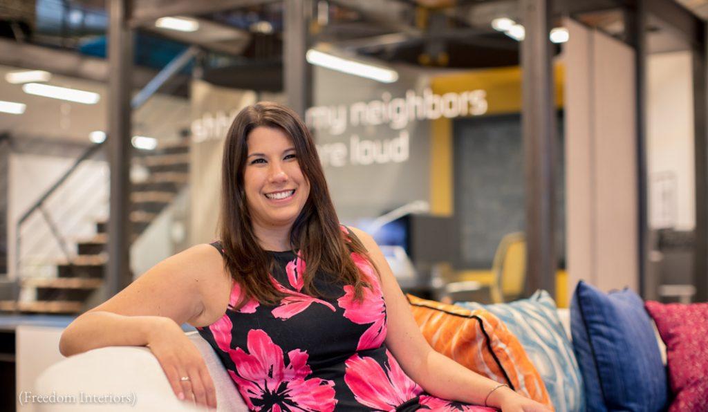 Une femme souriante, assise sur un canapé (Freedom Interiors)