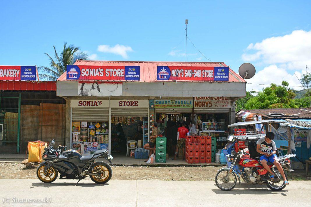 Homem sentado em uma moto no lado de fora de uma loja de conveniência nas Filipinas (© Shutterstock)