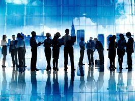 Des hommes et des femmes d'affaires debout, en train de travailler sur leurs ordinateurs portables, vus en silhouette (© Shutterstock)