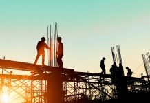 Siluet pekerja yang berdiri di atas infrastruktur (© yuttana Contributor Studio/Shutterstock)