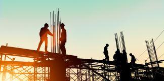 Silhueta de pessoas paradas em canteiro de obra (© yuttana Contributor Studio/Shutterstock)