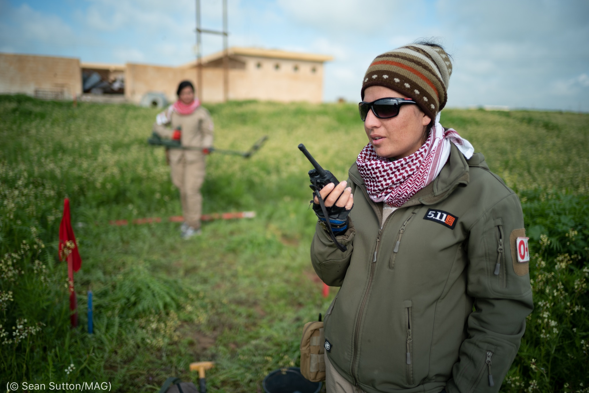 Women in field holding radio and metal detector (© Sean Sutton/MAG)