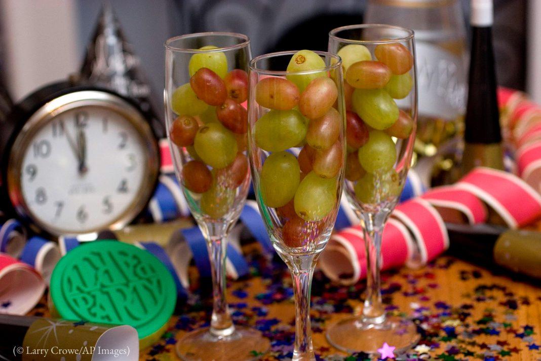 Trois flûtes à champagne remplies de grains de raisin avec un réveil à minuit moins cinq en arrière-plan (© Larry Crowe/AP Images)