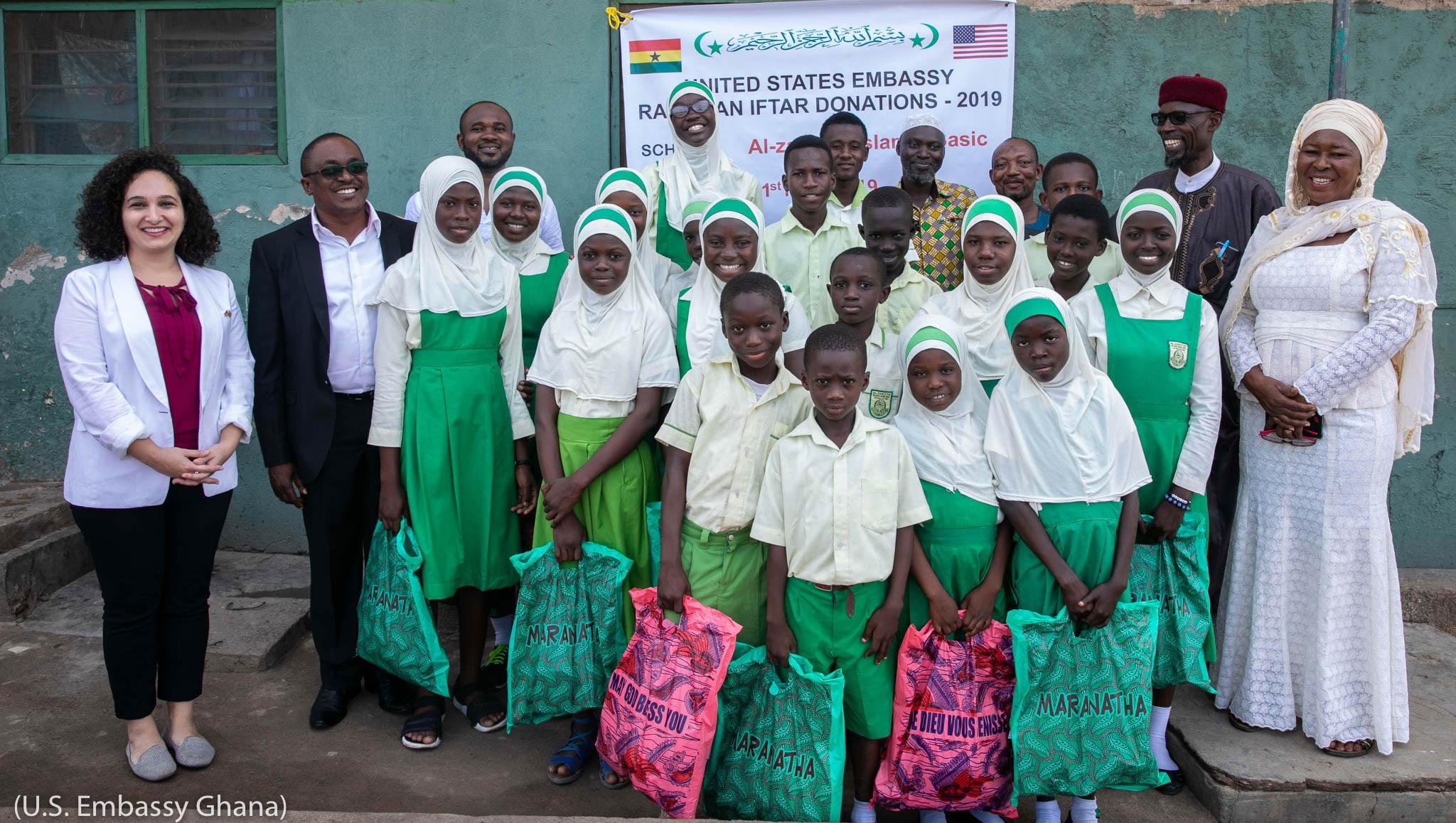 گروپ فوٹو کے لیے طالبات کے ساتھ کھڑے بالغ افراد۔ (U.S. Embassy Ghana)