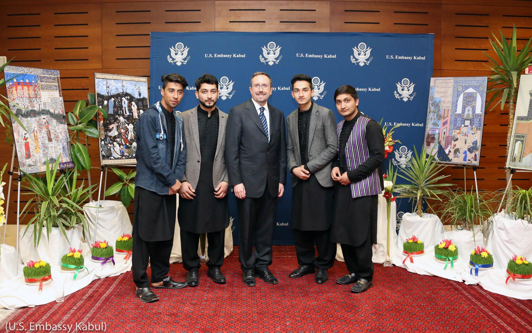 نوروز کی سجاوٹوں کے سامنے تصویر کے لیے کھڑے پانچ مرد۔ (U.S. Embassy Kabul)