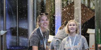 Mulheres jovens observam jato de água impulsionar bola no ar (© Capt. Grant Peehler/USMC)