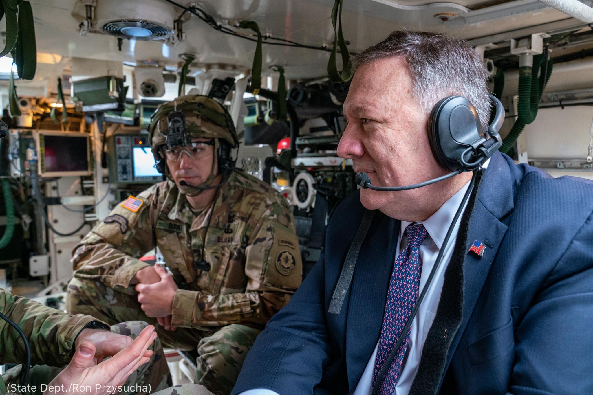 Secretário Pompeo usando fones de ouvido e sentado com pessoas em uniformes militares (Depto. de Estado/Ron Przysucha)