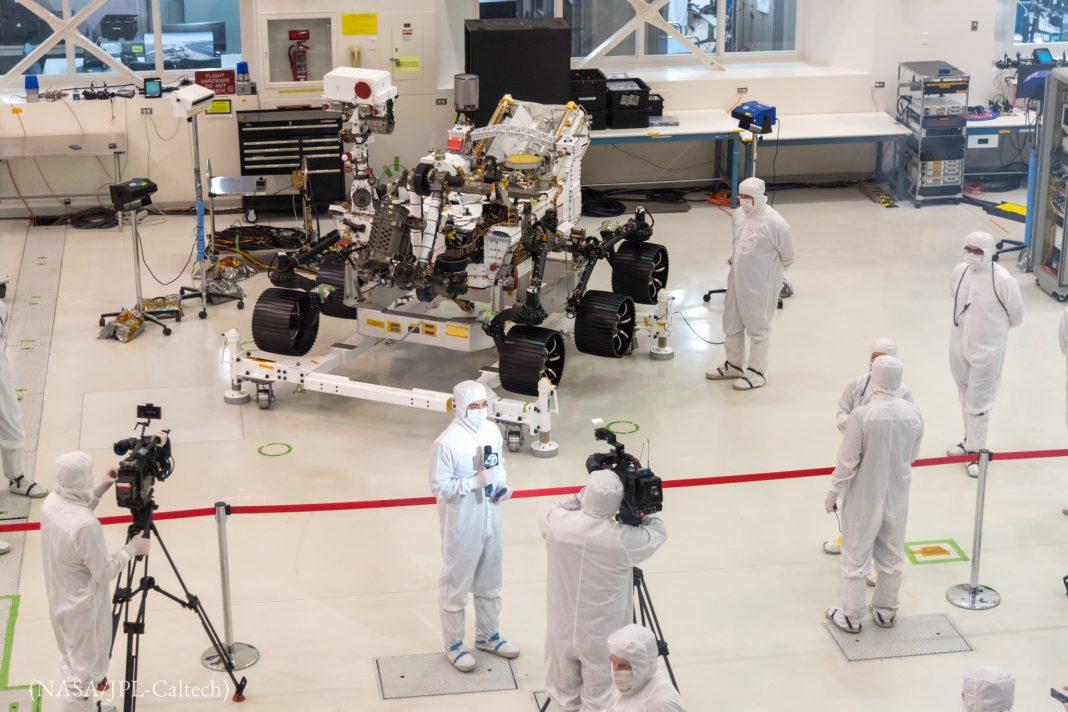 Personas con trajes blancos de pie junto a un vehículo con ruedas (NASA/JPL-Caltech)
