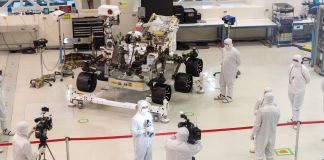 People in white suits standing by wheeled machine (NASA/JPL-Caltech)