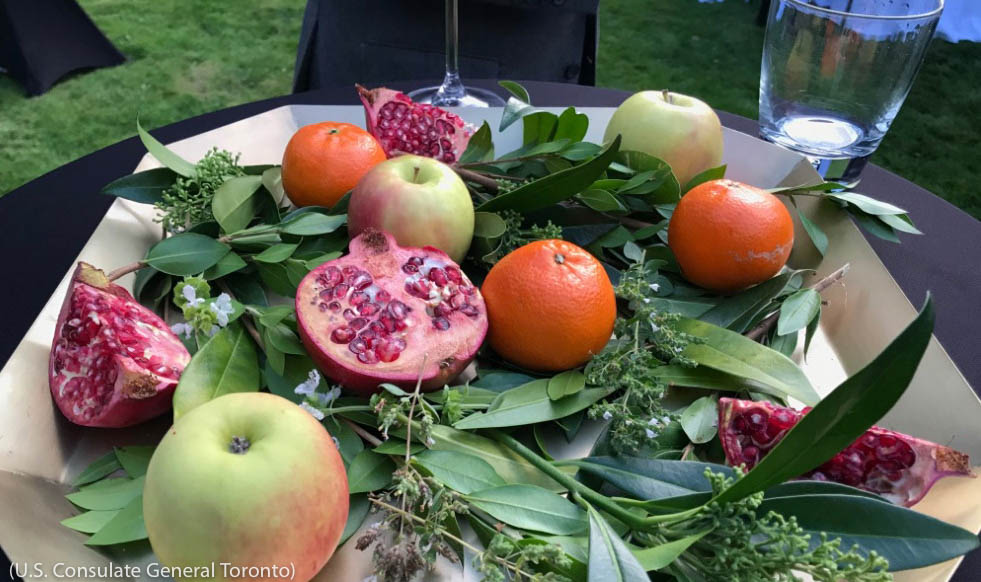 پلیٹ میں رکھے پتوں پر پڑے ہوئے پھل۔ (U.S. Consulate General Toronto)