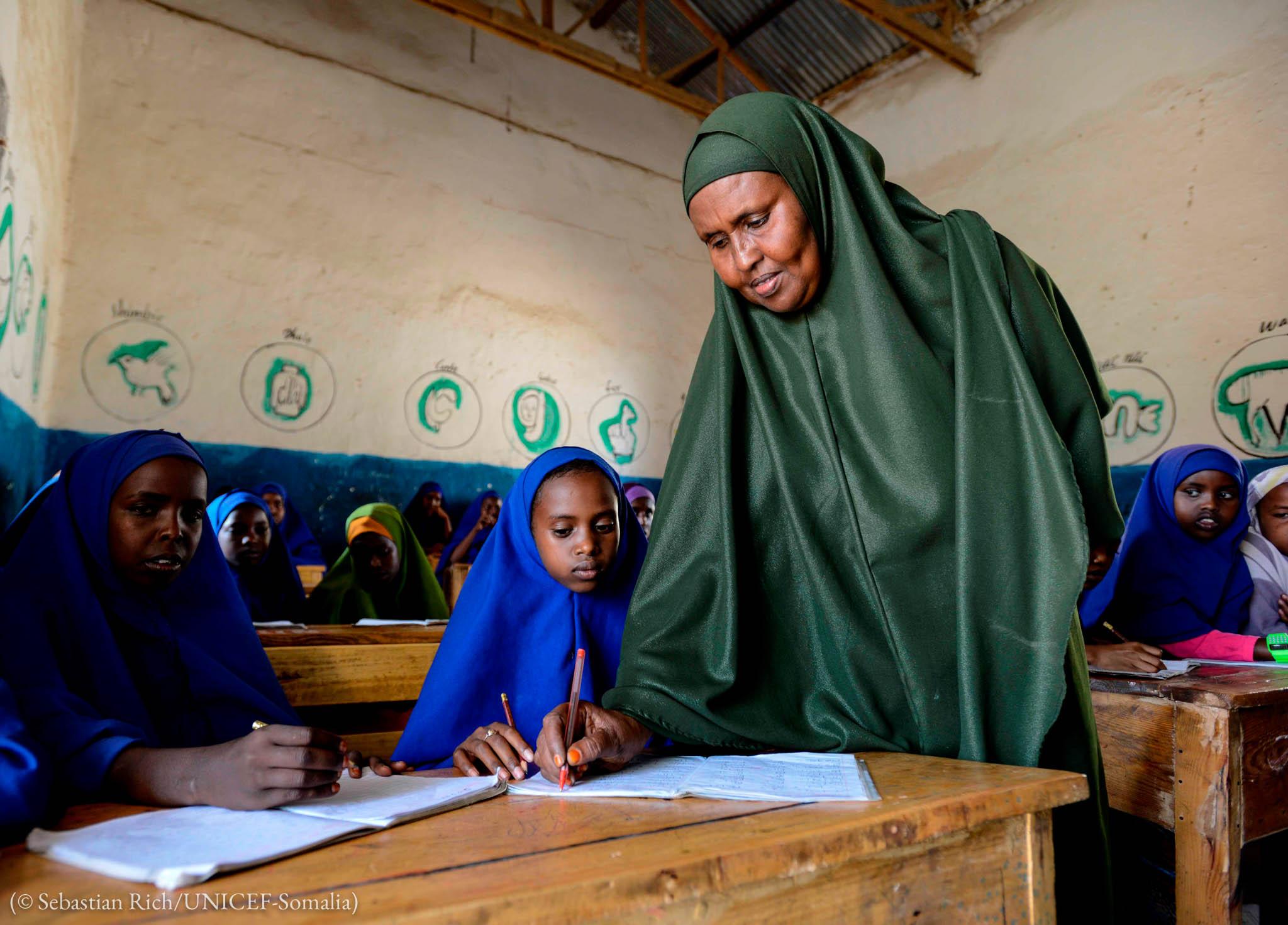 一名教师在教室里站在一个学生的课桌旁(© Sebastain Rich/UNICEF)
