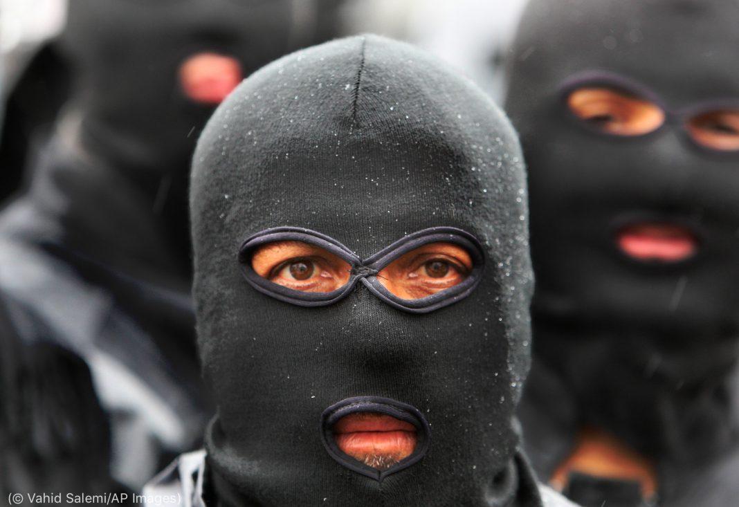Masked individuals (© Vahid Salemi/AP Images)