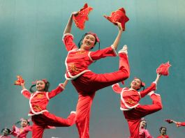 People wearing red costumes and dancing (© Mary Altaffer/AP Images)