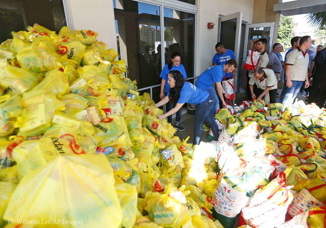Men and women sorting bags of food to be given away during a food drive (© Wilfredo Lee/AP Images)