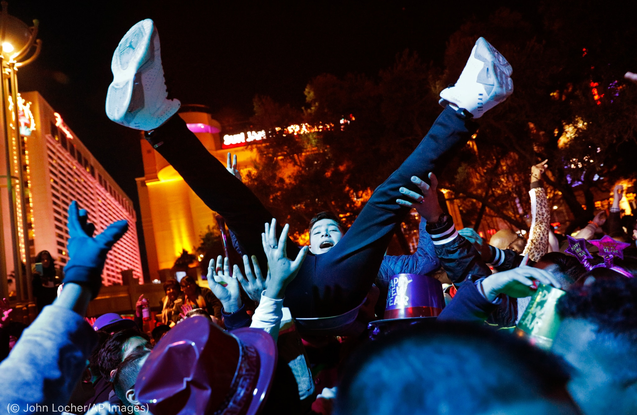 Man being held up in air by others (© John Locher/AP Images)