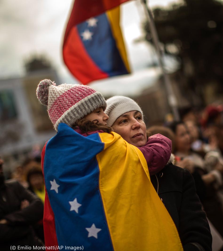 وینیز ویلا کے پرچم میں لپٹی ہوئی بچی ایک عورت کی بانہوں میں۔ (© Emilio Morenatti/AP Images)