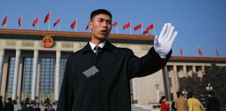 A soldier in an usher uniform stops journalists from getting too close to the Great Hall of the People