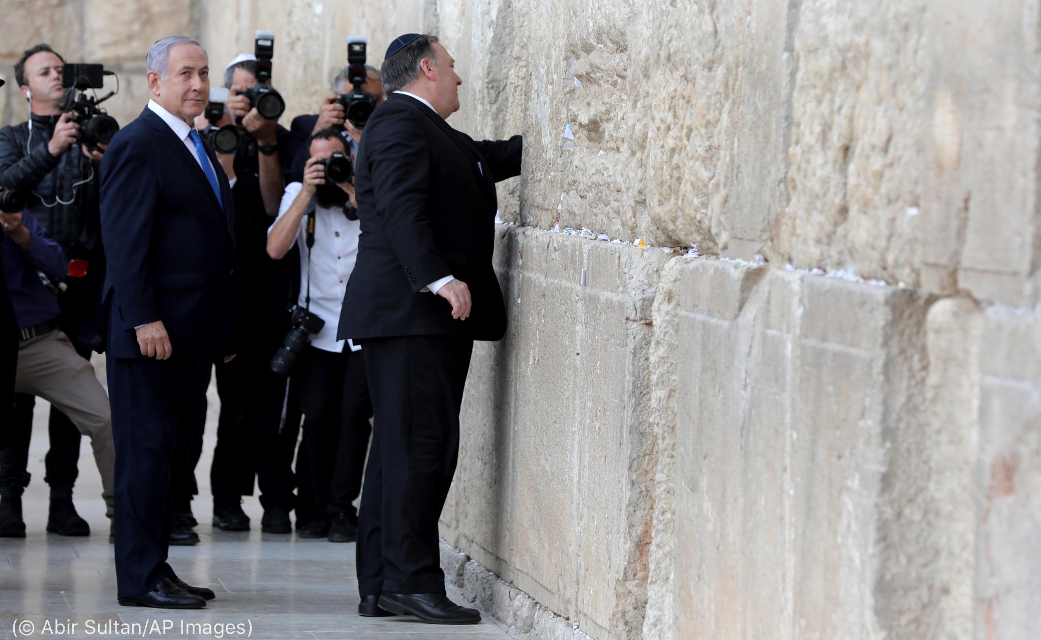 Secretário Pompeo estende o braço para tocar um muro de pedra (© Abir Sultan/AP Images)
