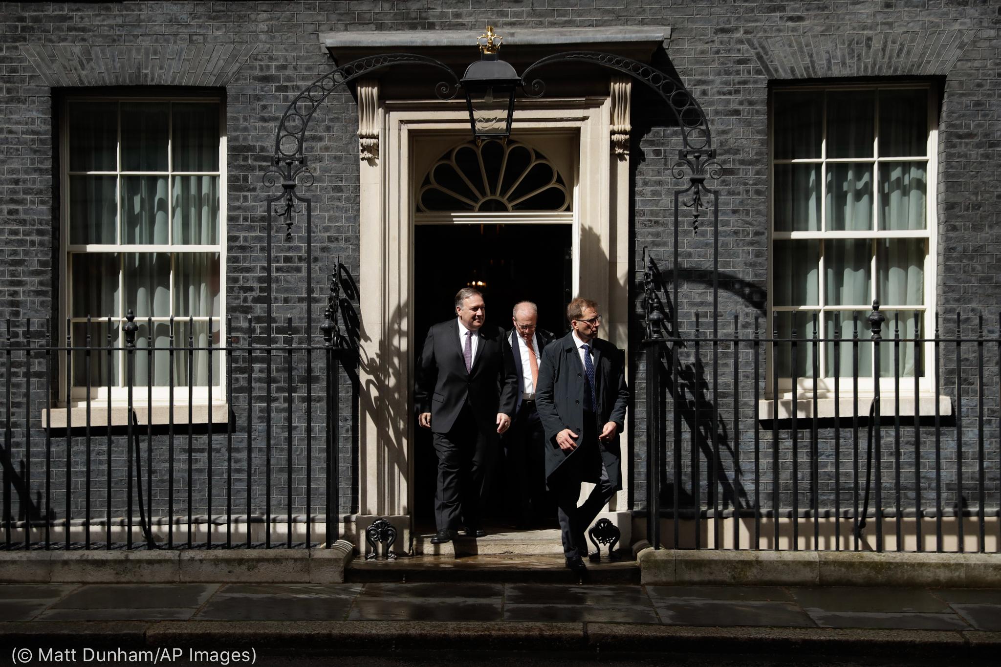 Três homens saindo de um edifício (© Matt Dunham/AP Images)