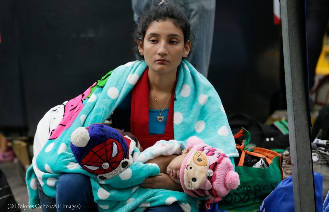 A Venezuelan migrant woman holding a baby outside an immigration processing office (© Dolores Ochoa/AP Images)