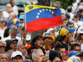 Woman waving a Venezuelan flag in the center of a group of people (© Leonardo Fernandez/ AP Images)