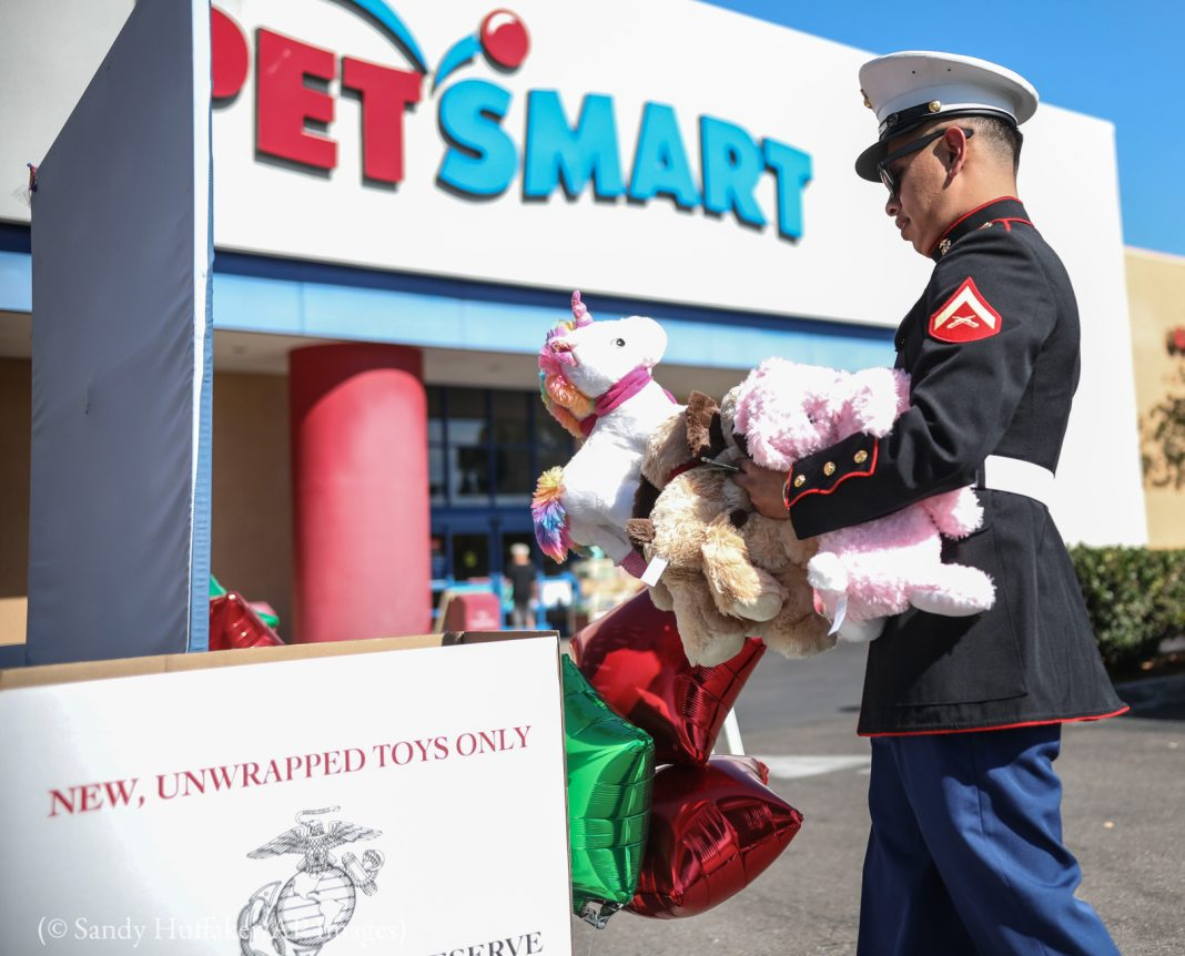 U.S. Marine dropping off toys in front of a store for a toy drive (© Sandy Huffaker/AP Images)
