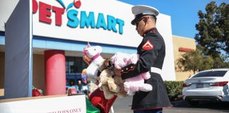 Un officier du Corps des Marines déposant des peluches à un point de collecte devant un grand magasin (© Sandy Huffaker/AP Images)