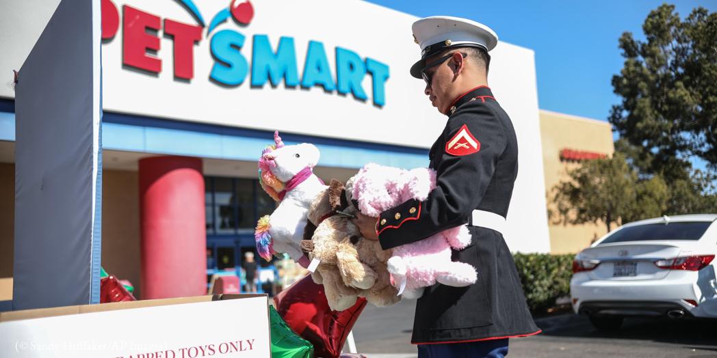 Fuzileiro naval dos EUA deixa brinquedos em frente a uma loja para uma campanha de arrecadação de brinquedos (© Sandy Huffaker/AP Images)