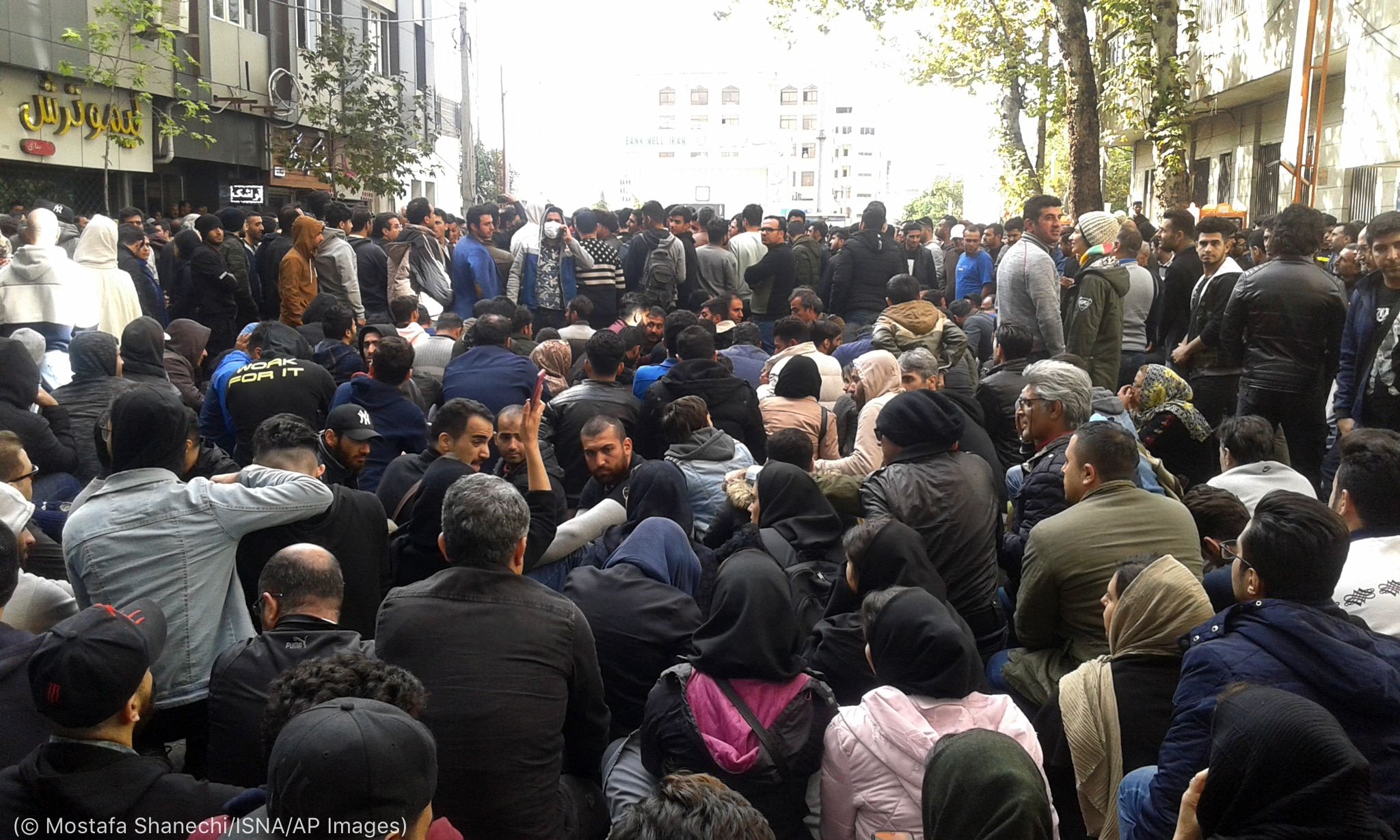 Dense crowed of people sitting and standing in street (© Mostafa Shanechi/ISNA/AP Images)