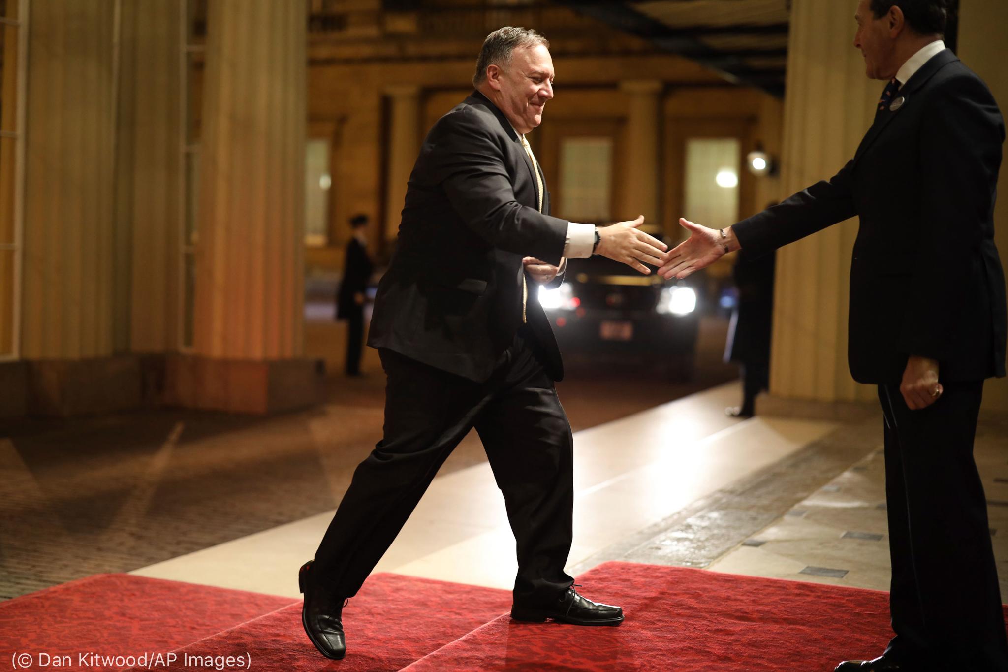 Secretário Pompeo andando em tapete vermelho com o braço estendido (© Dan Kitwood/AP Images)