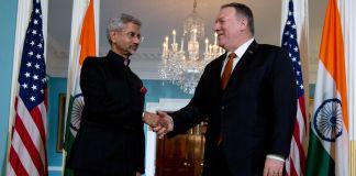 امریکی اور بھارتی پرچموں کے سامنے دو آدمی ہاتھ ملا رہے ہیں۔ (© Jose Luis Magana/AP Images)