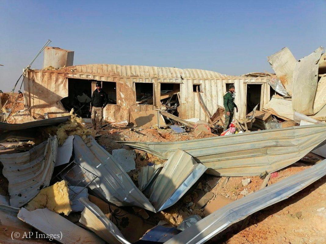 لوگ تباہ شدہ عمارت کے ملبے کو دیکھ رہے ہیں۔ (© AP Images)