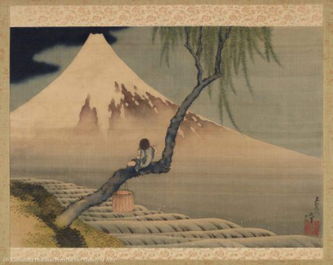 Pintura mostra menino sentado no tronco de uma árvore perto de uma montanha (© Katsushika Hokusai/Galeria de Arte Freer|Sackler)