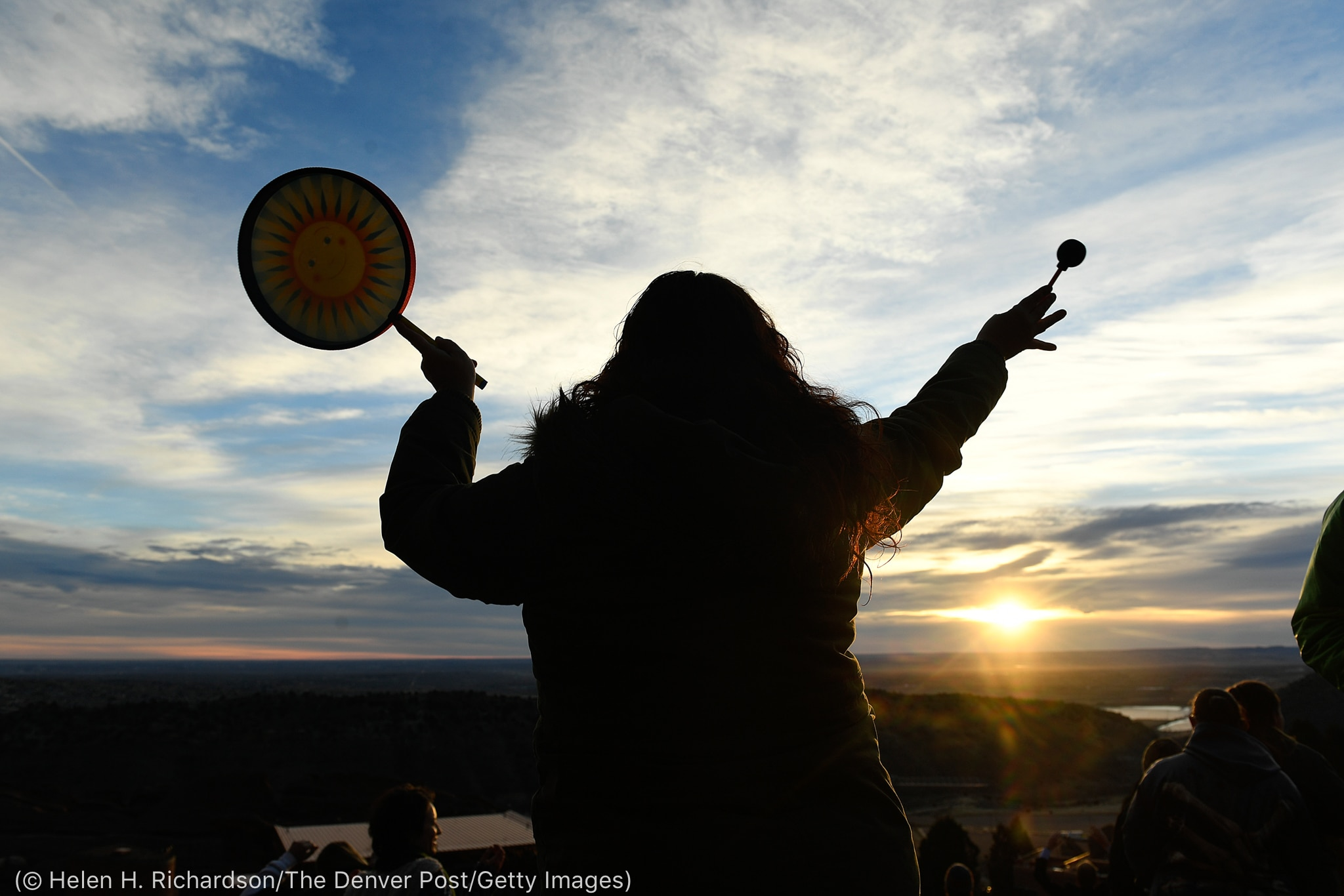 Woman playing drum with sun on horizon (© Helen H. Richardson/The Denver Post/Getty Images)