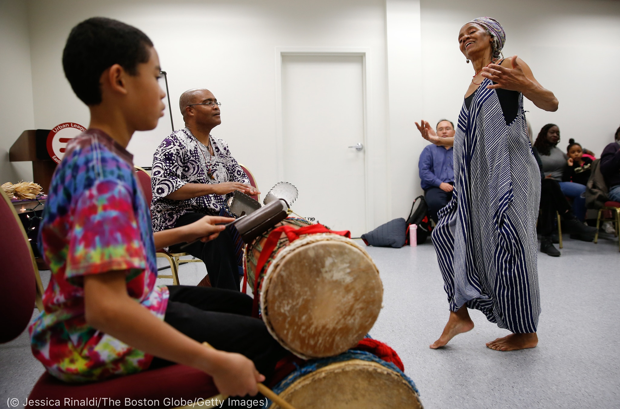 Woman dancing as other people play music (© Jessica Rinaldi/The Boston Globe/Getty Images)