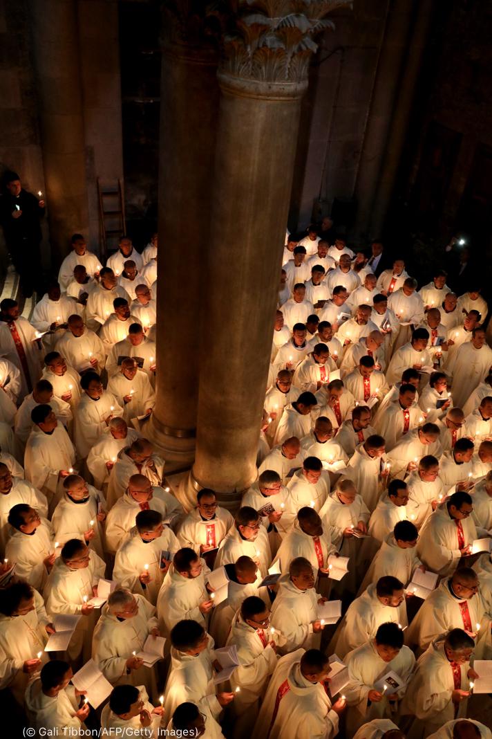 سفید کپڑوں میں ملبوس ہاتھوں میں موم بتیاں اٹھائے قریب قریب کھڑے لوگوں کی بلندی سے لی گئی تصویر۔ (© Gali Tibbon/AFP/Getty Images)