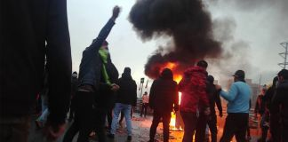 Protesters gathered around fire and smoke (© AFP/Getty Images)