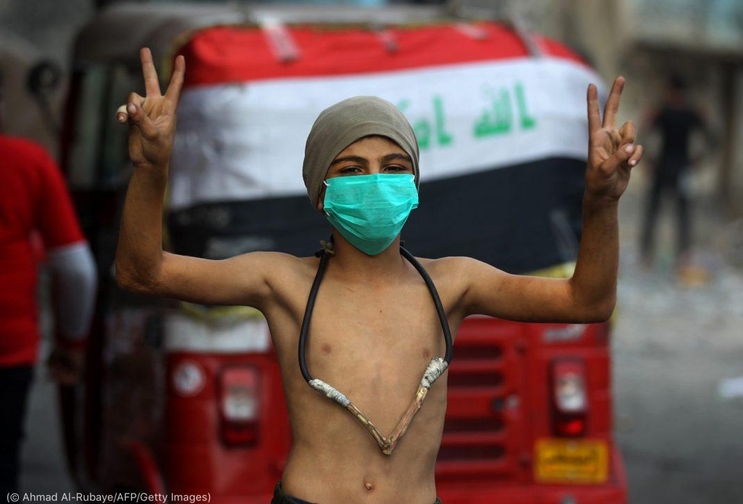 Menino sem camisa, com máscara cirúrgica e estilingue pendurado no pescoço, faz o sinal da paz (© Ahmad Al-Rubaye/AFP/Getty Images)