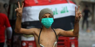 A shirtless child wearing a surgical mask and a slingshot around his neck making peace signs (© Ahmad Al-Rubaye/AFP/Getty Images)