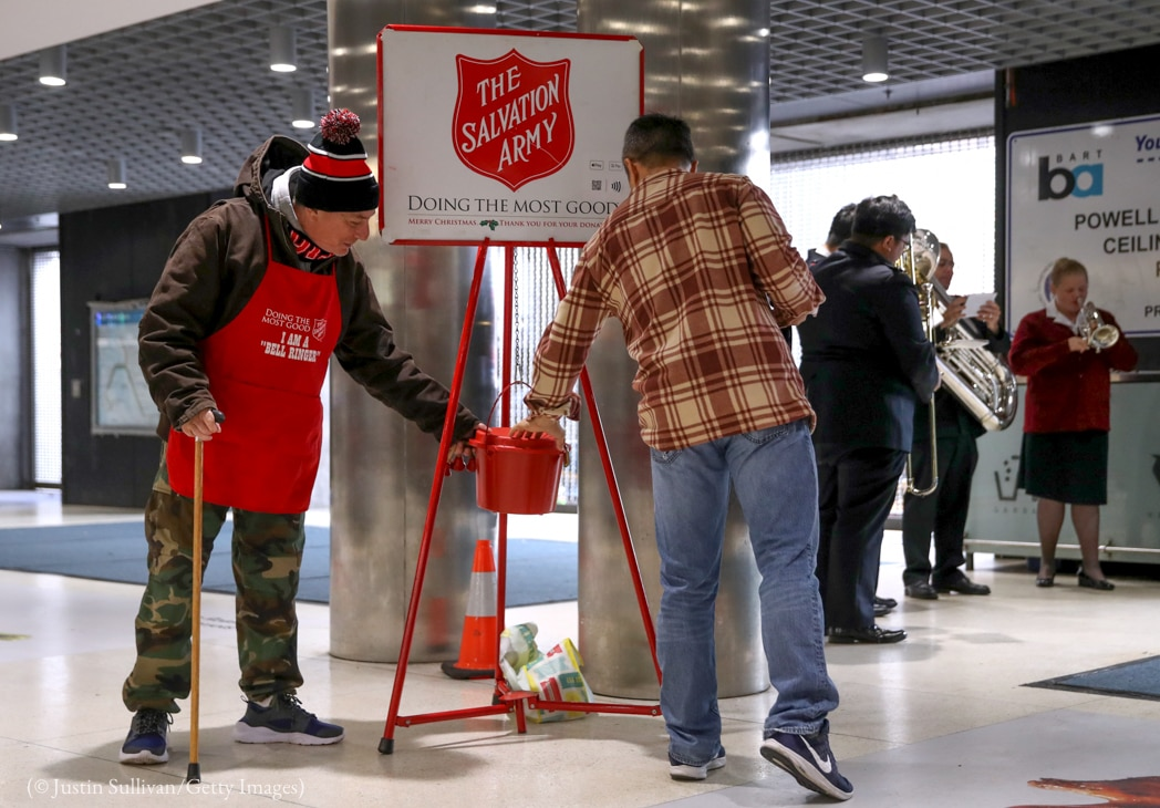 Man putting donation into Salvation Army red kettle (© Justin Sullivan/Getty Images)