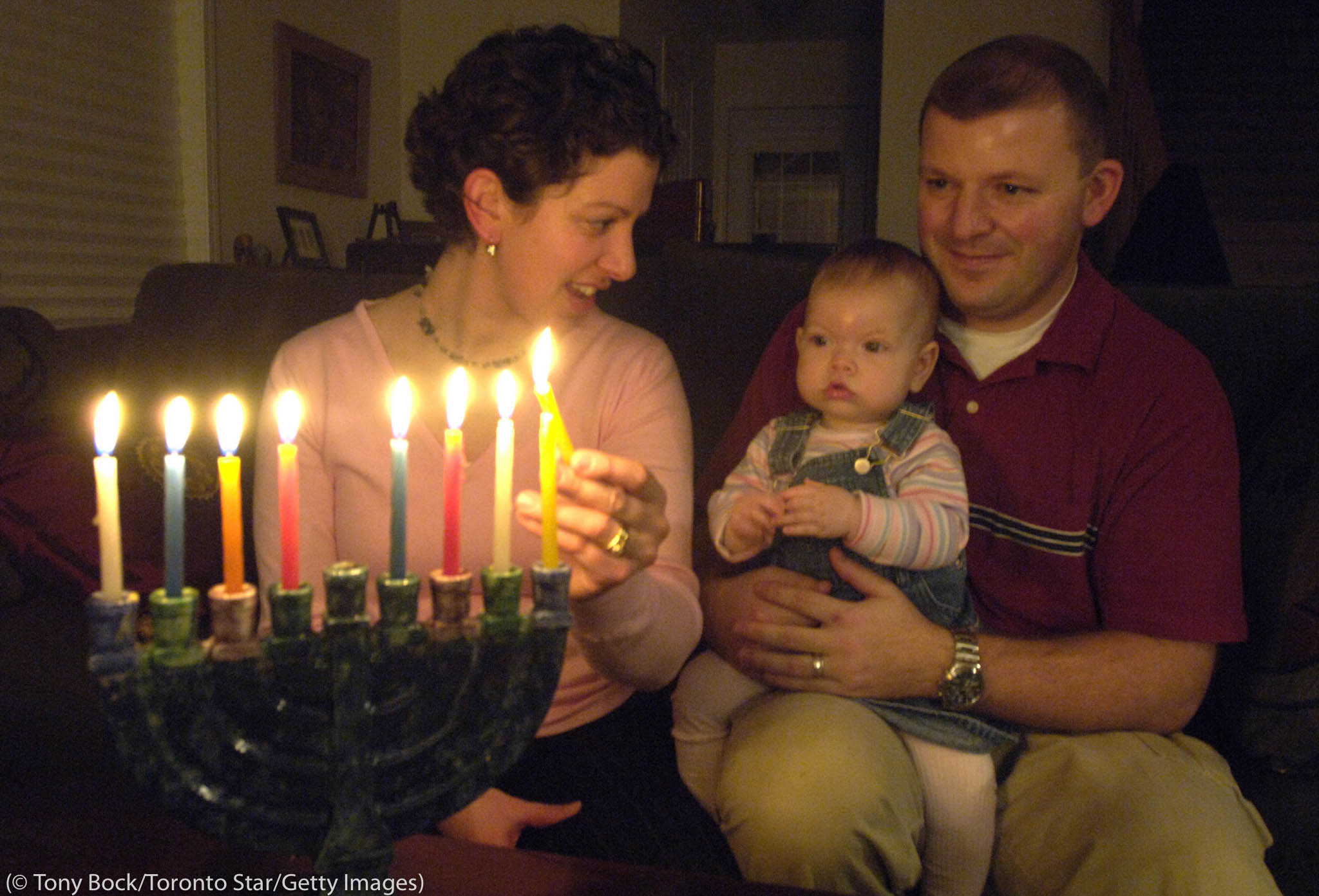 Parents with child on lap lighting menorah (Tony Bock/Toronto Star/Getty Images)